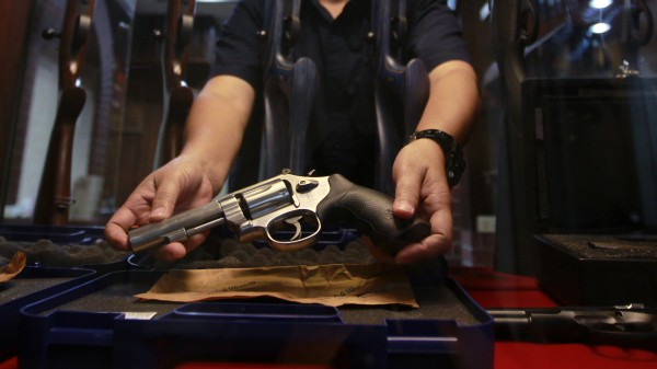 A shopkeeper shows a gun for sale in Bangkok October 12, 2012.