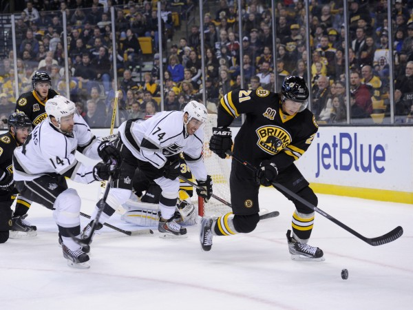 Boston Bruins left wing Loui Eriksson (21) tries to control the puck while being defended by Los Angeles Kings right wing Justin Williams (14) during the first period at TD Banknorth Garden in Boston Monday.