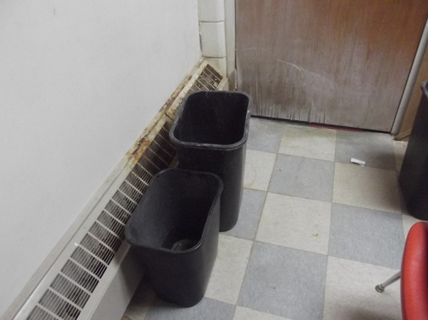Trash cans are used to collect rain water from leaking roof at Beatrice Rafferty School.