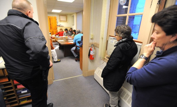 People stand in the hallway while listening to an East Millinocket Board of Selectmen meeting on Monday evening at the town office.