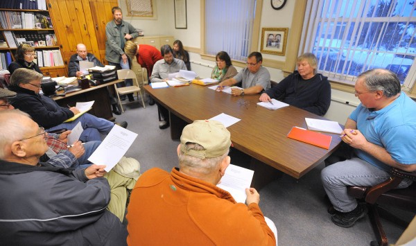 People listen the East Millinocket Board of Selectmen (sitting around table) meeting on Monday evening at the town office.