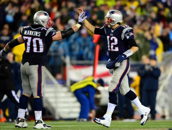 New England Patriots quarterback Tom Brady (12) celebrates with guard Logan Mankins (70) after a touchdown during the fourth quarter of the 2013 AFC divisional playoff football game against the Indianapolis Colts at Gillette Stadium.