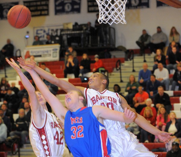 Mount Ararat High School's Kevin Carter (center) reaches for a rebound with Bangor High School's Xavier Lewis (right) and Justin Smith during their game Friday night at Red Barry Gym in Bangor.
