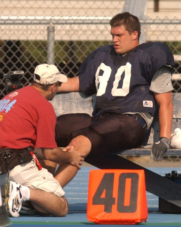 Josh Radulski of the University of Maine is evaluated by head trainer Paul Culina after injuring his left knee during an intrasquad scrimmage in August 2004 in Orono.