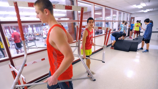 Bangor High School indoor track and field athletes Evan Brewer (left) and Felix Rivera move the hurdles before practice in the halls of the school Friday afternoon.