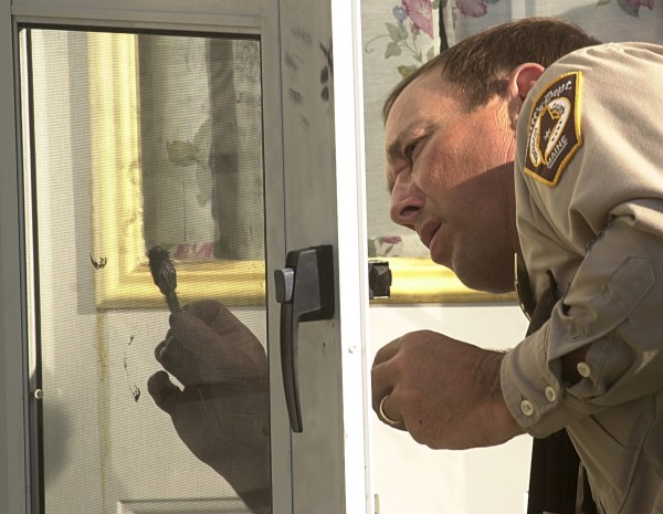 Chief Deputy Glenn Ross of the Penobscot County Sheriff's Office dusts for prints on the door of the Wentworth residence in Clifton in 2001.