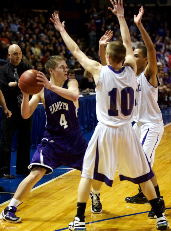 Senior guard Christian McCue of Hampden Academy looks for an opening through a pair of Deering High School defenders during the Class A Boys Basketball Championship game at the Cumberland County Civic Center in Portland March 3, 2012.