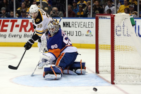Boston Bruins left wing Jordan Caron (38) and New York Islanders goalie Kevin Poulin (60) watch as a shot sails wide of the net during the third period of a game at Nassau Veterans Memorial Coliseum in Uniondale, N.Y., Monday night. The Bruins defeated the Islanders 6-3.