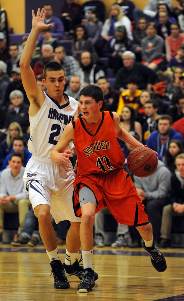 Brewer's Jamison Rhoads-Doyle drives to the basket while being closely guarded by Hampden's Zach Gilpin on Thursday at Hampden. Hampden won 67-33.