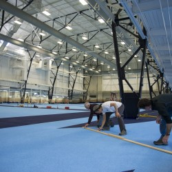 Workers prepare to paint lines on the track Thursday afternoon at the University of Maine's New Balance Field House in Orono. The facility, which is undergoing a $5 million renovation, is expected to be ready for the Penobscot Valley Conference-Eastern Maine Indoor Track League meets on Saturday.