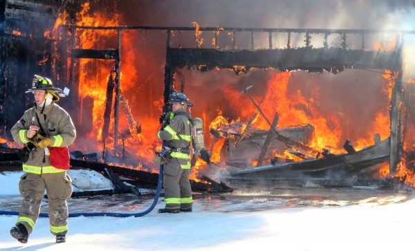 Firefighters attempt to battle the blaze that engulfed a Sullivan home on Friday morning. No one was in the home when the fire was reported, according to local fire officials.