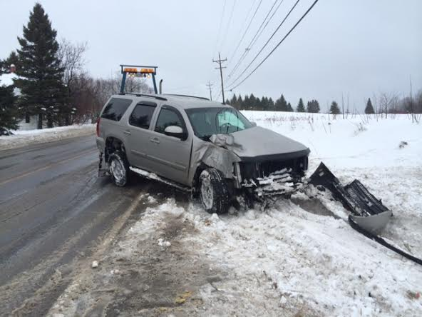 A 2007 Chevy Tahoe, driven by Laura Chase of Mapleton, is towed back onto the road after an accident on Route 163 in Mapleton on Monday. Chase spun out of control on an icy patch and hit a utility pole. She was not injured.