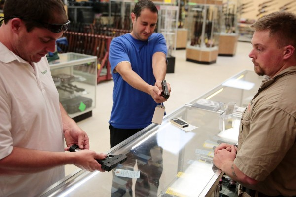 Sales associate Nick Ambroziak (right) assists Steven Beard, left, and Andy Spentzos with guns in July 2013, at Gat Guns in East Dundee, Illinois. A district judge on Monday ruled that a ban on gun sales in Chicago was unconstitutional.