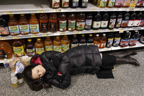 Karen Wang sleeps at the aisle of a Publix grocery store after being stranded due to a snow storm in Atlanta, Georgia, Jan. 29, 2014. A rare winter storm gripped the U.S. South on Wednesday, killing five people, stranding children overnight at their schools, gnarling traffic across many states and canceling flights at the world's busiest airport