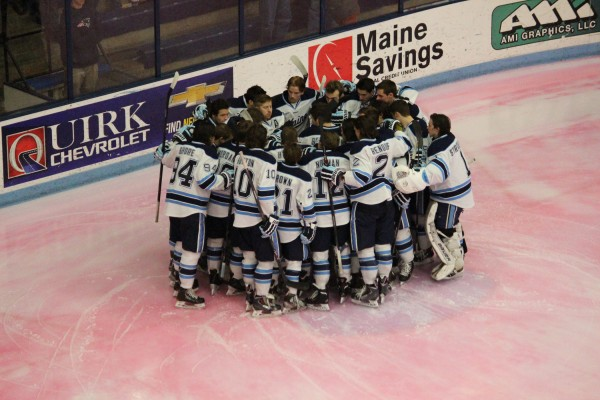 University of Maine hockey players huddle before Tuesday night's game against St. Francis Xavier at Alfond Arena in Orono. The exhibition game was played on pink ice as part of Hockey East's Staking Strives initiative for breast cancer awareness.