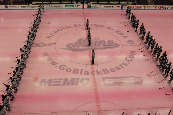 Member of the Maine and St. Francis Xavier hockey teams line up on the ice for national anthem at Alfond Arena in Orono Tuesday night. The exhibition game was played on pink ice as part of Hockey East's Staking Strives initiative for breast cancer awareness.
