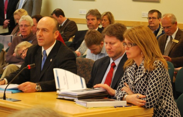 Gary Alexander (from left) and Eric Randolph of Rhode Island-based Alexander Group and Maine Department of Health and Human Services Commissioner Mary Mayhew prepare  to answer questions from the Health and Human Services Committee in Augusta on Jan. 14.