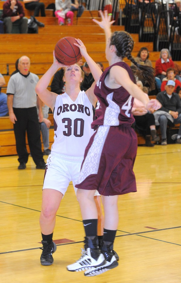 Mattanawcook Academy's Paige Hesseltine (right) tries to block a shot by Orono High School's Katie Smith during the girls' basketball game in Orono on Thursday.