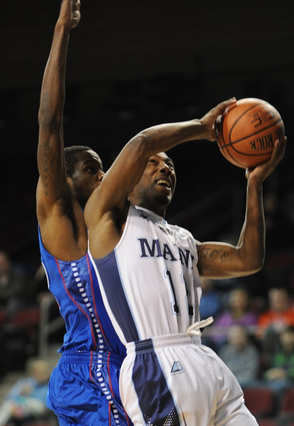 UMaine's Xavier Pollard puts up a shot against UMass Lowell's Antonio Bivins at the Cross Insurance Center on Thursday night
