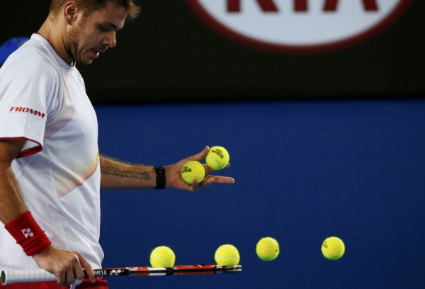Stanislas Wawrinka of Switzerland chooses balls for his service game during his men's singles quarter-final tennis match against Novak Djokovic of Serbia at the Australian Open 2014 tennis tournament in Melbourne.