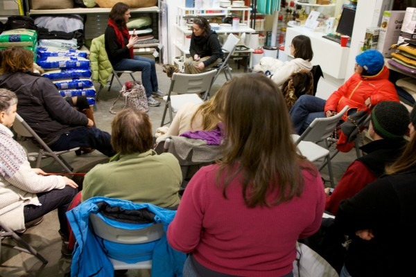 Pet communicator Sara Moore (back left) translates a dog's thoughts for its human owner Thursday night at Planet Dog in Portland. Proceeds from the event went to the nonprofit Planet Dog Foundation.