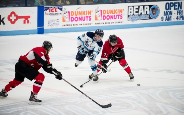 University of Maine's Blaine Byron tries to take control of the puck against University of New Brunswick's Mike Thomas (#71) and Taylor MacDougall (#22) during the first period of play at the Alfond Arena on Tuesday night.