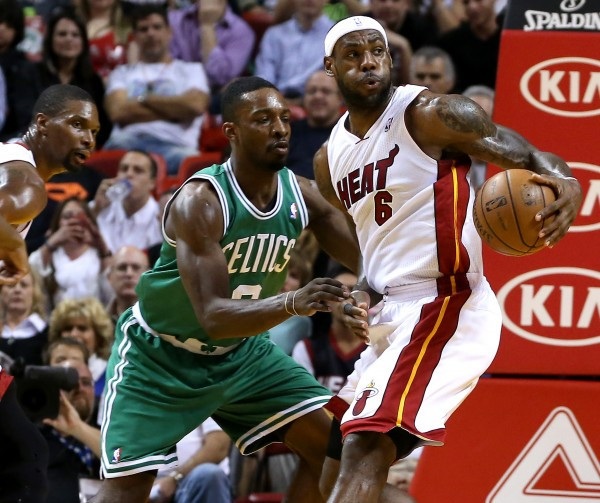 Miami Heat forward LeBron James (6) dribbles the ball as Boston Celtics forward Jeff Green (8) defends in the first half Tuesday night at American Airlines Arena.
