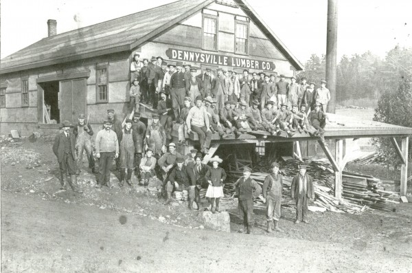 The crew of the Dennys River Lumber Company pose for a picture with ten year old Marie Mahar, who happened along just in time, in 1910.