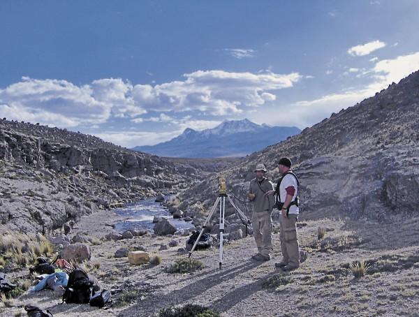 Kurt Rademaker (left) and Peter Leach stand along the Arma River at about 4,500 meters in elevation. Rademaker is using surveying equipment to map an archaeological site at the bedrock cliff at left. The harness worn by Leach, a UMaine Climate Change Institute alum, is used with with ground-penetrating radar, which detects buried features in sites.