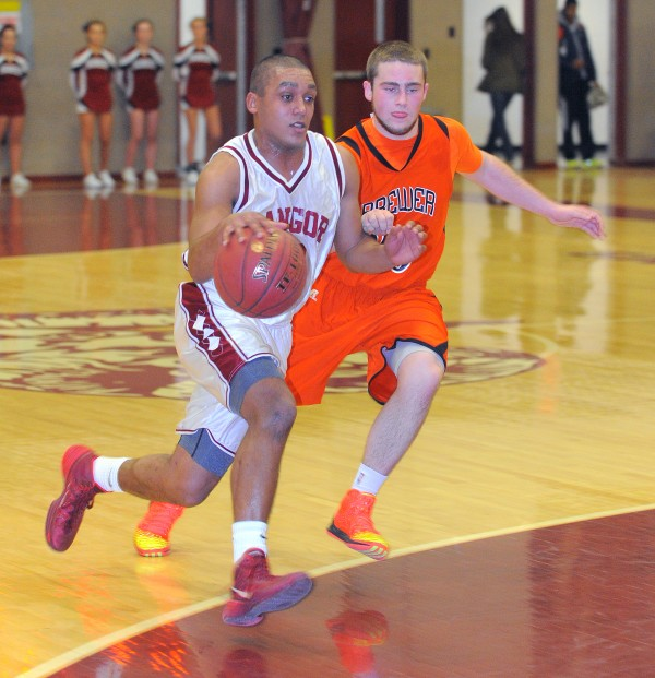 Bangor High School's Xavier Lewis (left) drives past Brewer High School's Brendan Newcomb during the boys basketball game in Bangor Wednesday evening.