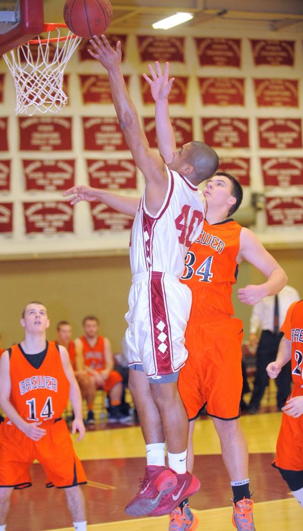 Bangor High School's Xavier Lewis (left) drives for the basket past Brewer High School's Matt Pushard during the boys basketball game in Bangor Wednesday evening.