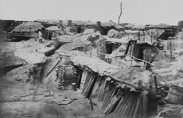In mid-spring 1865, Timothy O'Sullivan photographed three civilians — two men and a woman — inspecting the recently abandoned Union entrenchments outside Petersburg. As evidenced by the wood doors and the crude chimneys blending barrels, mud, and wood, Union soldiers actually lived in this section of trenches. By now Robert E. Lee had surrendered his army at Appomattox, and the fighting was over in Virginia.