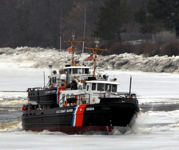 The Coast Guard cutter Tackle (WYTL 65604) rides high on the ice between Brewer and Bangor Saturday while opening the Penobscot River's deep water channel in conjunction with the cutter Bridle (WYTL 65607), located beyond the Tackle.