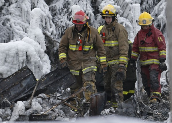 Emergency workers walk through the remains of the senior residence Residence du Havre in L'Isle Verte, Quebec, Jan. 25, 2014. Thirty-two people are presumed to have died in the fire that swept through a retirement residence in the Canadian province of Quebec on Thursday, police said on Saturday.