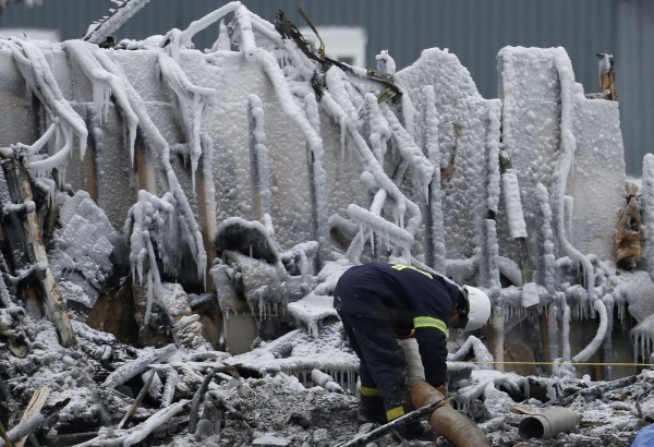 An emergency worker digs through the remains of the senior residence Residence du Havre in L'Isle Verte, Quebec, Jan. 25, 2014. Thirty-two people are presumed to have died in the fire that swept through a retirement residence in the Canadian province of Quebec on Thursday, police said on Saturday. Eight bodies have been recovered.