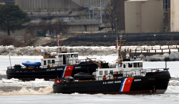 The Coast Guard cutters Tackle (right) and Bridle (left) work jointly Saturday to break the ice jamming the Penobscot River's deep water channel between Brewer and Bangor (background).