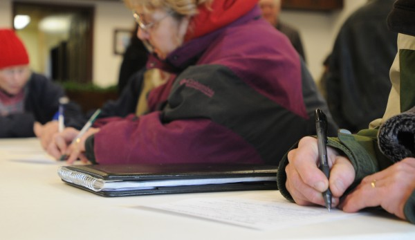 People fill out information forms at the Dexter Town office Saturday. A group of former shoe company executives and public officials are planning to revive some shoe manufacturing the the town.