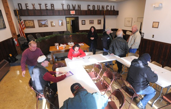 People fill out information forms at the Dexter Town office Saturday. A group of former shoe company executives and public officials are planning to revive some shoe manufacturing the town.