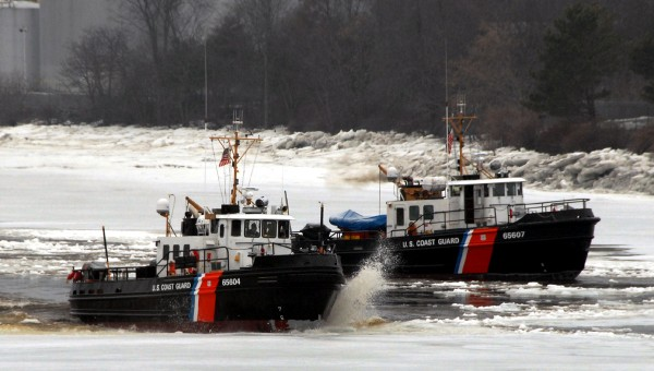 Shattered ice and water fly as the Coast Guard cutter Tackle (WYTL 65604) drives onto the ice between Brewer and Bangor while opening the Penobscot River's deep water channel in conjunction with the cutter Bridle (WYTL 65607).