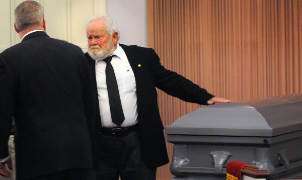 Bill Knight's longtime friend and fellow Troop Greeter Jerry Mundy puts his hand on Knight's casket at the end of the funeral service at Brookings-Smith funeral home in Bangor Sunday. Knight died in December of 2013 at the age of 91.