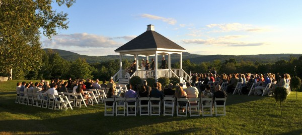 As a wedding takes place in The Lucerne Inn gazebo, guests watch the ceremony from the surrounding chairs. The inn is a popular wedding location.