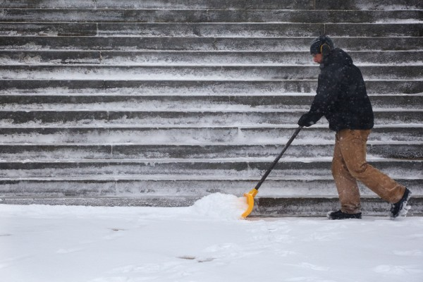 Patrick Farrell clears the steps of Portland City Hall during Thursday's snowstorm.