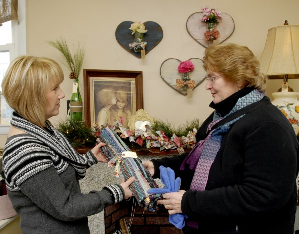 Inside Fine & Dandelion at 4 Plymouth Road, Carmel, owner Sherelle McIntyre (left) displays a braided rug for a customer shopping at the vintage retail and gift shop on a cold Saturday, Jan. 4.