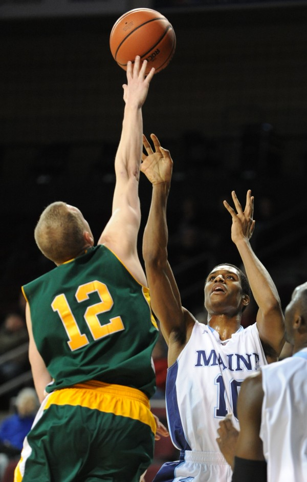 UMaine's Shaun Lawton gets his shot blocked by Vermont's Sandro Carissimo during first-half action on Thursday night at the Cross Insurance Center in Bangor.