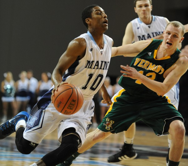 UMaine's Shaun Lawton dribbles to the basket while guarded by Vermont's Sandro Carissimo during first-half action on Thursday night at the Cross Insurance Center in Bangor.
