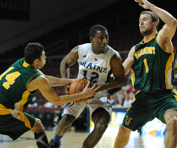 UMaine's Xavier Pollard drives to the basket with heavy pressure from Vermont's Josh Elbaum, left, and Brian Voelkel, right, during first-half action on Thursday at the Cross Insurance Center in Bangor.