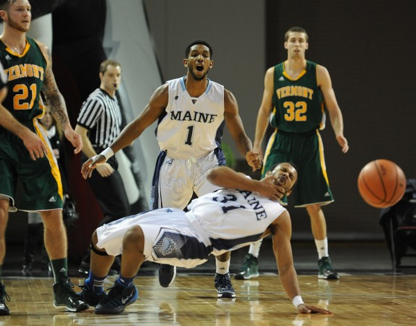 UMaine's Troy Reid-Knight falls to the floor after getting hit by Vermont's Canon Rusin, left, during first-half action on Thursday at the Cross Insurance Center in Bangor.