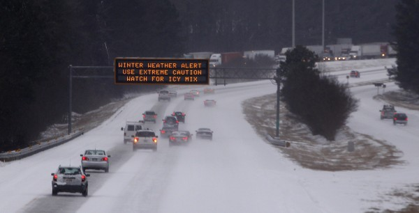 Cars drive under a traffic sign displaying winter storm warnings after a rare snowstorm in Kennesaw, Georgia, January 28, 2014.