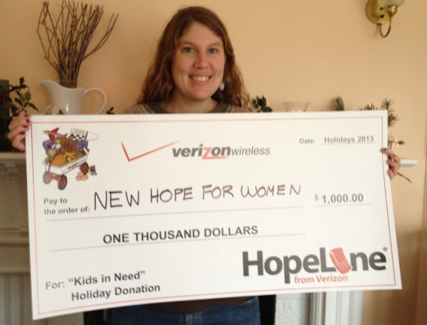 New Hope for Women's Transitional Services Advocate, Hannah Ives, holds a $1,000 HopeLine grant check from Verizon Wireless.