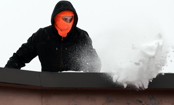 Danny Demmons of Demmons Roofing in Charleston, shovels snow and ice off of a roof in sub zero temperatures Thursday afternoon on May Street in Bangor. &quotMy hands are froze,&quot said Demmons. &quotBut I'd rather be doing this than sitting at home.&quot